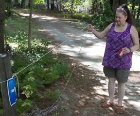 Rebecca Smith shows the rope her family used to make it down their driveway toward their house as the raging White River washed past them, almost five feet high. VTD Photo/Taylor Dobbs