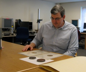 State archivist Scott Reilly sits in front of the Vermont coat of arms die cut by Tiffany's in the early 1860s. Photograph by Nancy Graff.