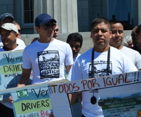 """Migrant workers hold up signs depicting Vermont driver's licenses at a bill-signing Wednesday in Montpelier that allows them to obtain """"operator's privilege cards"""" so they can drive in the state with or without documentation. Photo by Alicia Freese/VTDigger"""