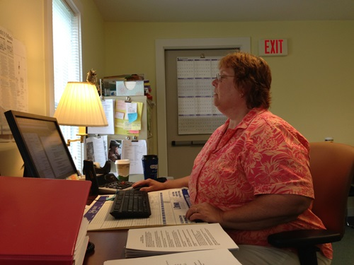 Cheryl Brown, administrative assistant for the Moretown Town Clerk's Office, works on the town's latest Irene-related project in the temporary town office near the town landfill. Photo by John Herrick/VTDigger