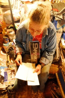 Beverly Grout reviews the journal she keeps on the backs of torn ammunition boxes and finds her notes of when she and her husband were paid for each load of timber. Photo by Hilary Niles/VTDigger