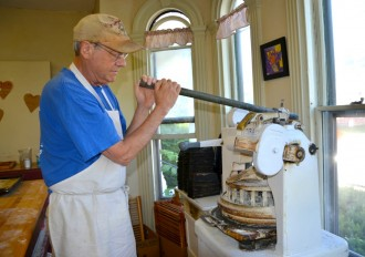 Michael Sherman works the lever on an ancient roll-forming machine at Manghis' Bakery in Montpelier, where the longtime professor, author and historian enjoys a very different career as a baker. Photo by Andrew Nemethy