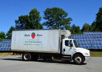 One of Black River Produce's fleet of 50 refrigerated trucks with the trademark logo parks in back of the company headquarters in North Springfield. Black River ships to some 3,000 clients in Vermont and parts of New Hampshire and Massachusetts. The solar array can provide up to 80 percent of the firm's power needs. Photo by Andrew Nemethy