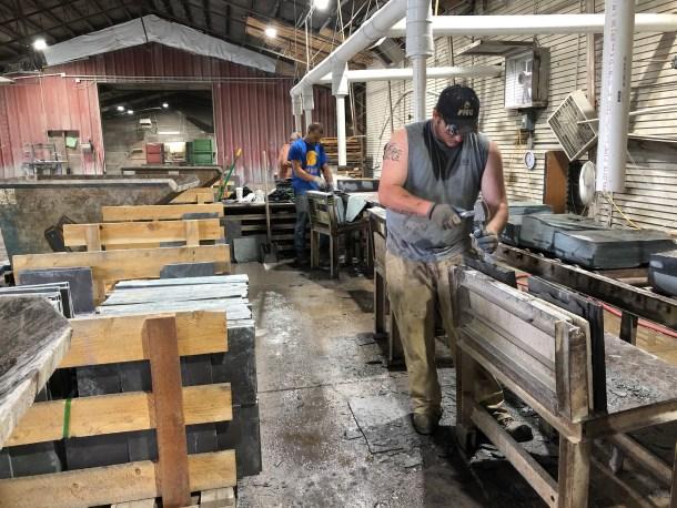 Workers hand-shape slate