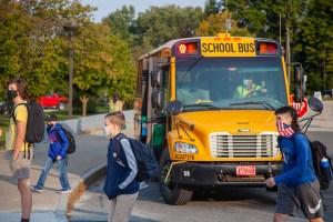 Students walk by school bus