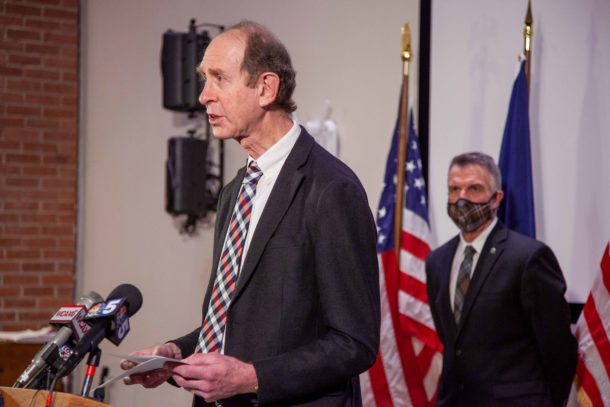 Mark Levine at podium, with Phil Scott
