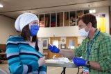 Woman showing shoulder to EMT holding sterile wipe