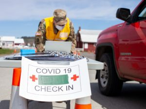 "Red truck approaches table with sign reading ""covid 19 check in"""